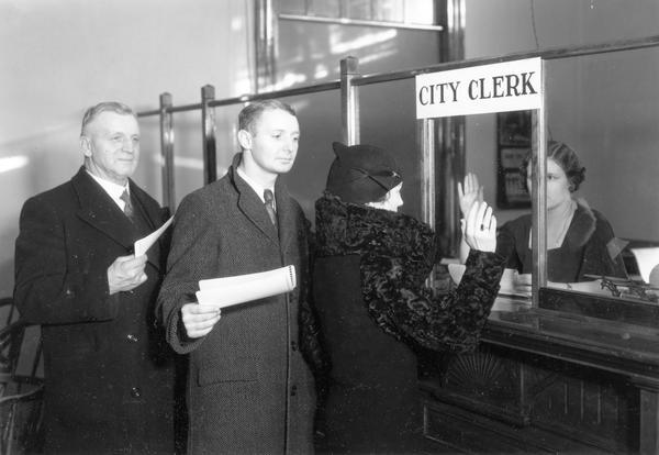 Citizens line up at the City Clerk office to register to vote while a woman raises her hand to take the oath.
