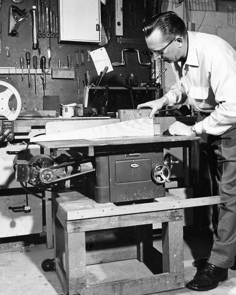 A man cuts a block of wood on a table saw in his workshop.