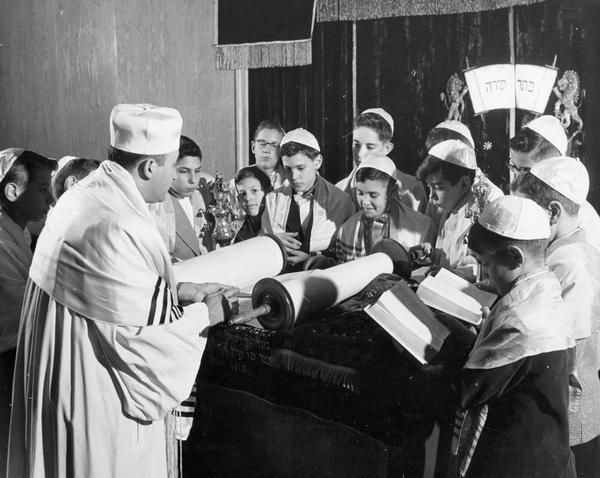 Rabbi Max Lipschitz, and a group of Bar Mitzvah students wearing prayer shawls and yarmulkes, (Jewish skullcaps) gather around the torah on the altar to read prayers at the Beth Israel Center shortly after its opening.