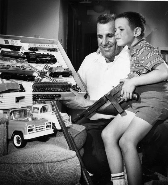 Boy holds toy gun and looks at electric train set and toy train with older man.