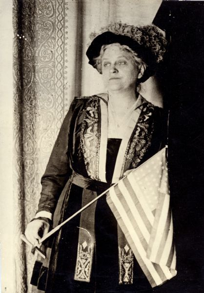 Carrie Chapman Catt, suffragist and peace advocate, holding an American flag.