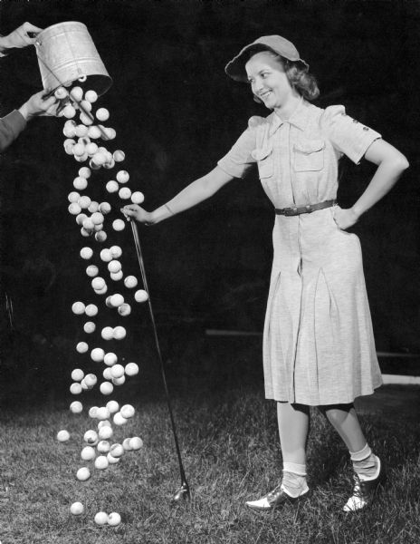 A woman dressed to play golf smiles as a bucket of golf balls is spilled at her feet.  This is one of several demonstrations of strobe light functions at Frank Scherschel's Strobo Research Lab.