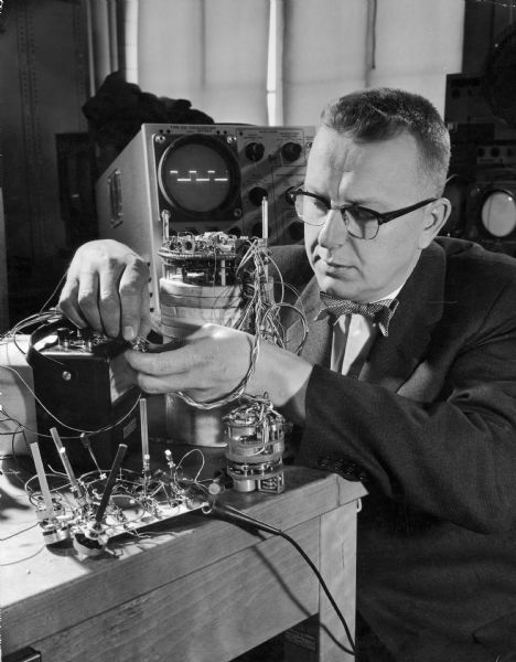"""Doc"" Edgerton adjusts equipment in the lab. Known for his pioneering work in the development of the electronic flash, his photograph of a splashing milk-drop is his best known work."