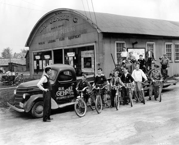 WW II scrap metal drive. Scoutmaster Edward G. Shaw and his troop of boy scouts on bicycles and on a trailer loaded with scrap metal. The trailer is hitched to an International truck and is parked in front of a McCormick-Deering dealership operated by R.H. Gehrke Company. The Scouts helped collect scrap metal during Governor Julius P. Heil's MacArthur Week. The troop of eighteen boys was divided in four divisions and the boys went out among the farms on their bicycles. They stopped at various farms, asked permission to collect scrap and, when it was granted, gathered it in convenient piles to be collected later by the junk dealer's motor truck.