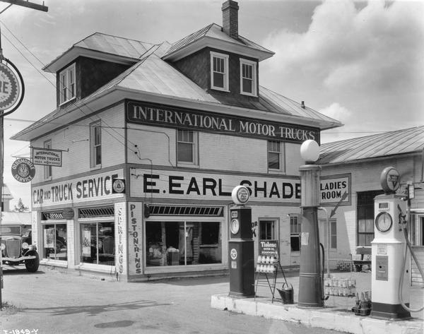 International motor truck dealership and service station of E. Earl Shade. Also attached is a gas station island with Purol Pep and Conoco pumps. The station also serviced Oldsmobile cars.