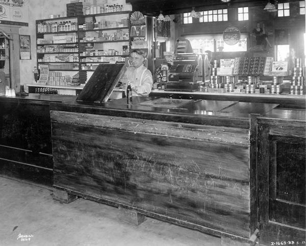 Male bartender at Clyde Cockersham's Bar. The bar was equipped with a McCormick-Deering ten can cooler.