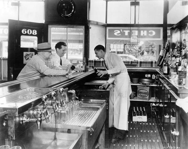 Two patrons and bartender at Chet's tavern. The bartender is pulling bottles of Schlitz beer out of an International No. 4 De Luxe dry type beverage cooler.