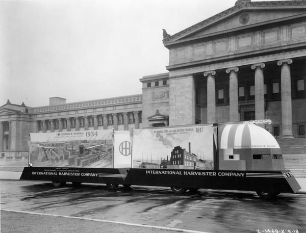 "International Harvester Company parade float for the ""A Century of Progress"" Worlds Fair. The two-section float is parked in front of the Field Museum and reads: ""McCormick's First Chicago Reaper Works, 1847, Annual Capacity 500 Reapers,"" and ""McCormick Works, 1934, World's Largest Farm Machine Factory."""