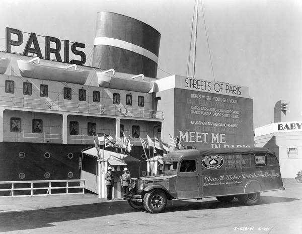 "International A-5 beer truck in front of ""Streets of Paris"" ocean-liner attraction at the ""A Century of Progress"" Worlds Fair. The truck was owned by Chas H. Wieber Distributing Company and advertises Canadian White Horse Ale and Schlitz beers."
