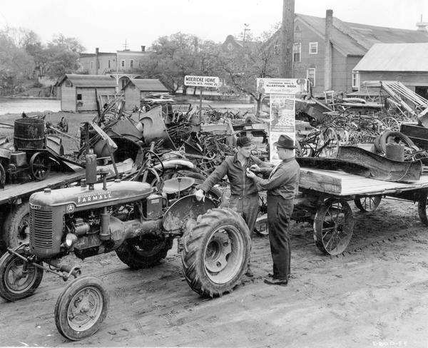 "Scrap drive at International Harvester dealer. Original caption: ""C.J. Moericke, who is dealer at Marion in the Green Bay territory, was receiving scrap from farmers in a stock pile to the rear of his establishment. Shipments by motor truck from this pile were made to junk dealer at Appleton. Some 15 tons of scrap were in the pile when pictures were taken. Mr. Moericke said he figured on handling a total of about 40 tons. The community was also building up a pile. Mr. Moericke is shown . . . pinning MacArthur button on Harold C. Kruger, who had just brought in a trailer loaded with scrap with his father's Farmall A."""