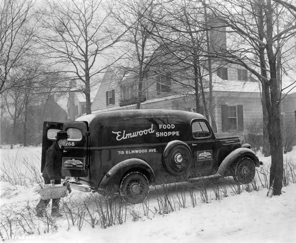 Employee of the Elmwood Food Shoppe making a home delivery with his International D-2 truck.
