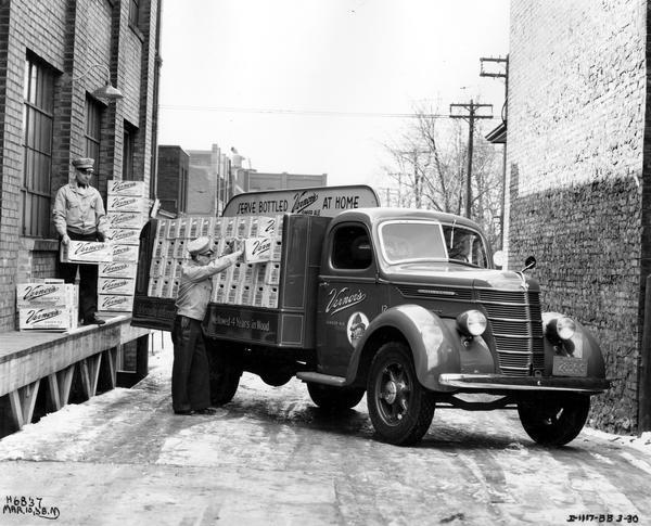 Two men loading cases of Vernon's ginger ale (soda) on an International D-30 truck in Toronto, Canada.