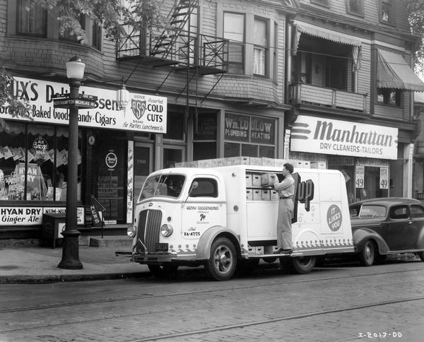 Man unloading cases of 7-Up soda outside a delicatessen at the corner of Michigan and Northampton streets. Truck operated by Henry Guggenheimer.