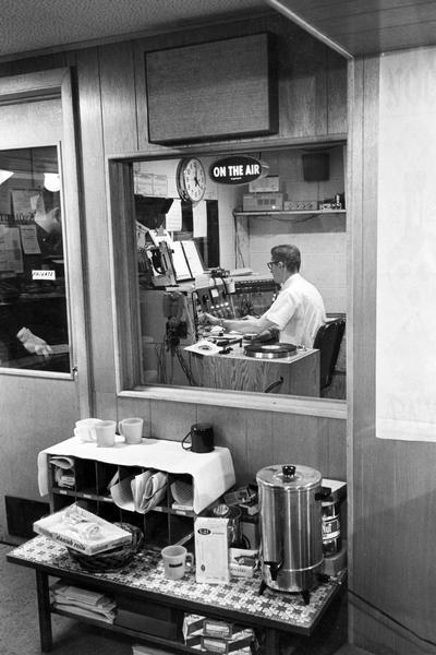 "Radio announcer Del Viney on the air inside Wisconsin's Very Live Radio (WVLR) station during the dinner music show. Caption reads: ""Dinner Music Show is announced by Viney, whose meal usually comes from snack table."""