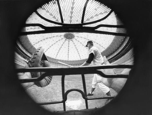 Paneled dome of Houston's Astrodome as seen through a baseball catcher's mask behind home plate.