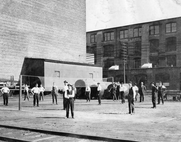 Employees of International Harvester's Deering Works take a break from a volleyball match outside the factory. The match pitted workers from the twine mill against those from the main office. Final score: twine mill 52, main office 27. The Deering Works was originally built by William Deering for the Deering Harvester Company in 1880. In 1902 it became International Harvester's Deering Works. The factory was located at Fullerton and Clybourn Avenues and closed in 1933.