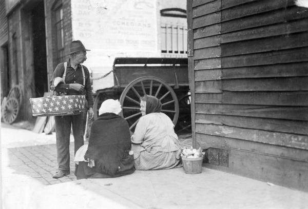 One man and two women on an urban sidewalk with baskets of produce. The man's basket is decorated with white stars on a dark field. The people are probably selling the produce on the street.