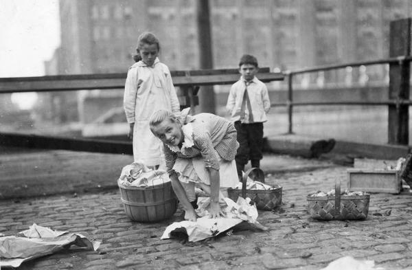 Young girl wrapping or unwrapping produce from baskets on an urban street, possibly in Chicago, Illinois. The girl is likely offering the produce. A boy and girl stand behind her looking on.