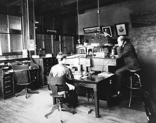 "Two men and a woman working in a branch(?) office of the International Harvester Company. One man is talking on a telephone. Portraits of William Deering and Cyrus McCormick are hanging on a wall, along with the poster ""Midnight at McCormick's."""
