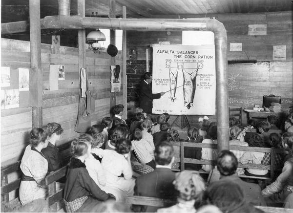 "International Harvester Agricultural Extension Department employee J.E. Waggoner delivers a lecture to children and farmers assembled at Providence School. A lecture chart titled ""alfalfa balances the corn ration"" helps Waggoner tell the story of the corn fed pig and of his twin brother who liked alfalfa with his corn. The school house has a partition to make two rooms."