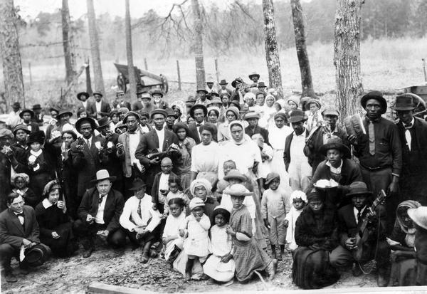 "African American tenant farmers assembled for a barbecue. The tenants worked for Louis Frank Sessions who appears in the front row, third from the left (wearing a light colored hat). To his right is Miss Helen Holden of Chicago. The barbecue followed a lecture by International Harvester's Agricultural Extension Department. According to the original caption, the tenants ""finished up the barbecue after the white folks had eaten their fill."" One man is holding a guitar and another is holding a violin (fiddle)."