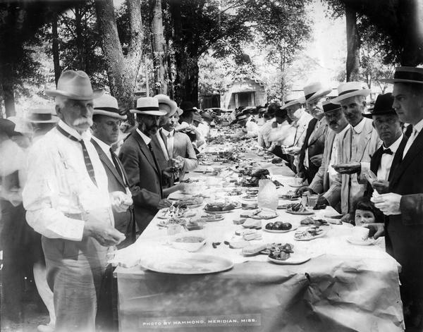 View down long table set up outdoors for a feast. Men are standing on both sides, and a young girl is standing between two men on the right.