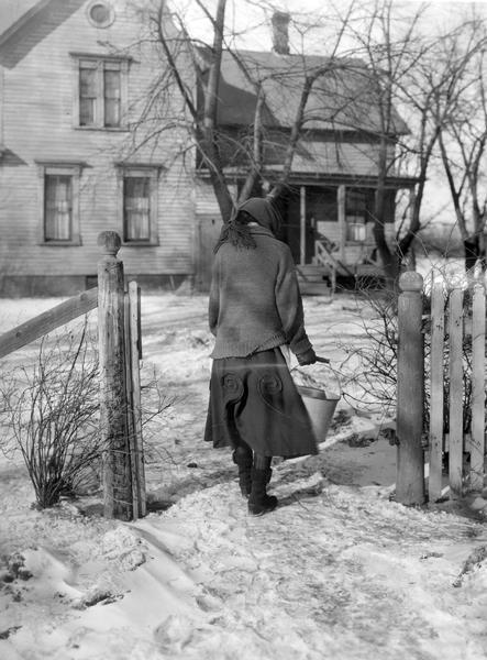 Woman carrying a bucket of water back to her farmhouse in winter.