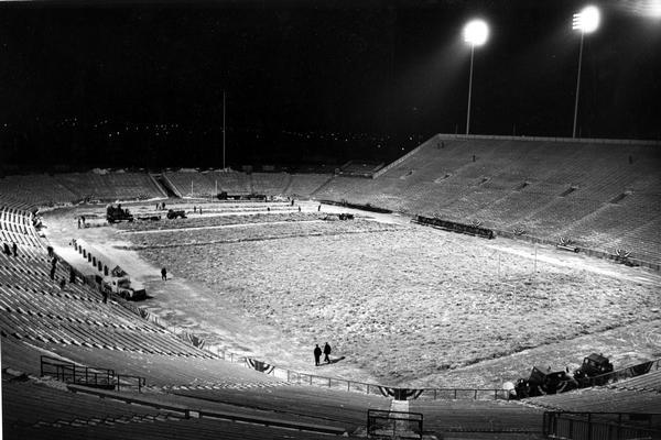 Workmen, shivering in the 6 a.m. predawn cold, remove hay from the field at Green Bay City Stadium (now Lambeau Field) before the NFL championship game between the Green Bay Packers and the New York Giants. The Packers went on to win the game 37-0. The hay, which formed a one-foot padding on top of the field tarpaulin, was used to protect the field and leave it green and dry for the game.  The men are using Farmall tractors and implements to remove the hay.