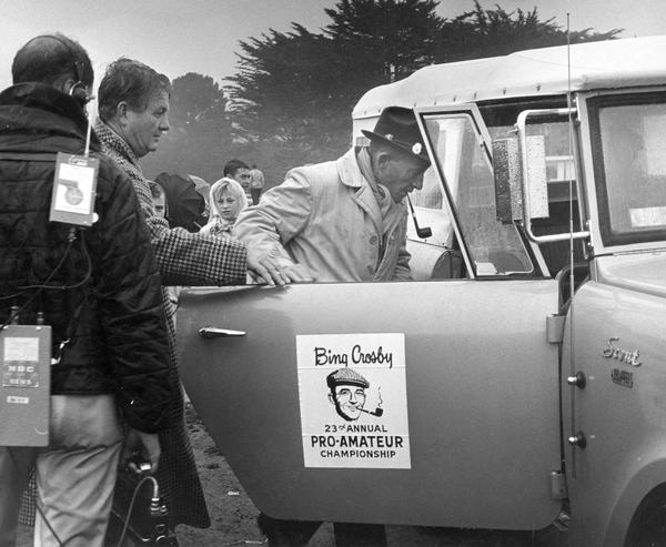 "Actor and singer Bing Crosby getting out of a drizzling rain and into an International Scout 4x4 pickup during his 23rd Annual Pro-Amateur Golf Championship, otherwise known as ""Crosby's Clambake."""