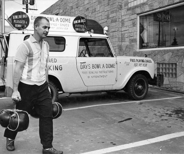 Man delivering serviced bowling balls from an International Scout truck. The truck was owned by Day's Bowl-A-Dome.