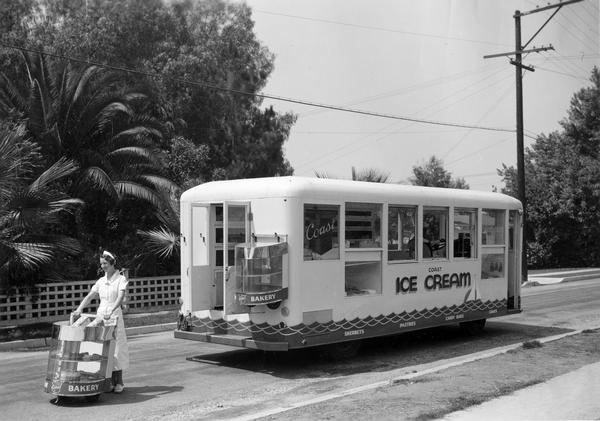 Female employee of the Coast Ice Cream Company delivering baked goods with a special bakery cart taken from the back of a specially modified International C-300 ice cream truck.  The truck features an approximate 130 inch wheelbase and 20 foot body.