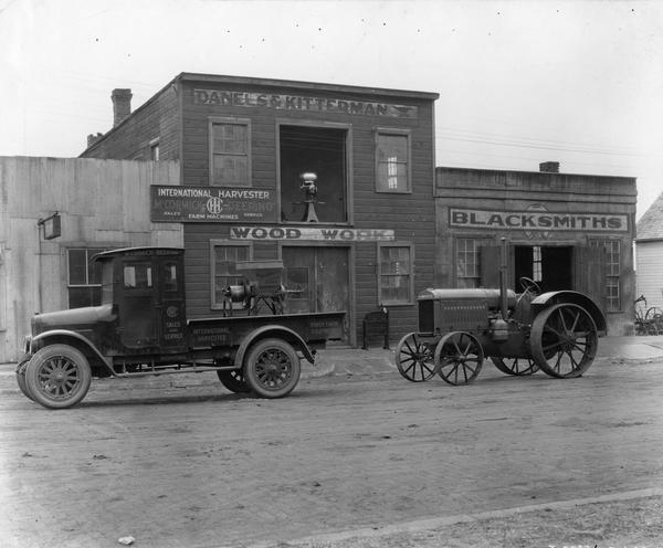 "International ""Red Baby"" (Model S) truck and McCormick-Deering 10-20 tractor in front of the dealership of Danels & Kitterman.  In the back of the truck is a McCormick-Deering feed grinder. Pictured in the background in the open second floor window is a McCormick-Deering cream separator."