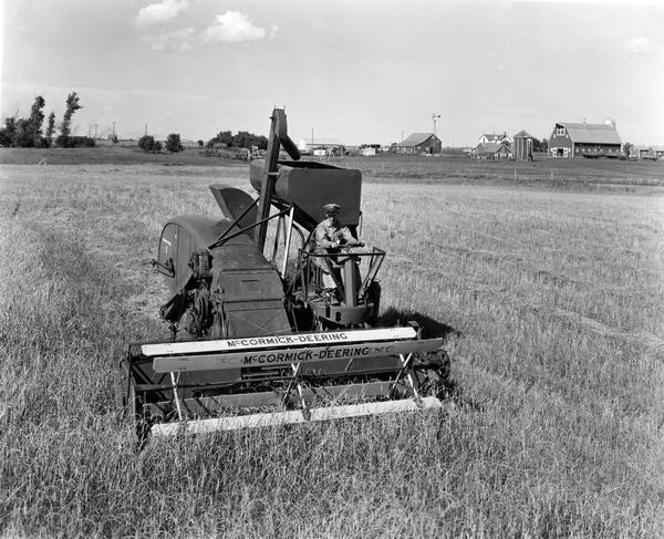 Slightly elevated view of farmer Ed Frey at the controls of a McCormick-Deering 123-SP combine on his 1400 acre farm.