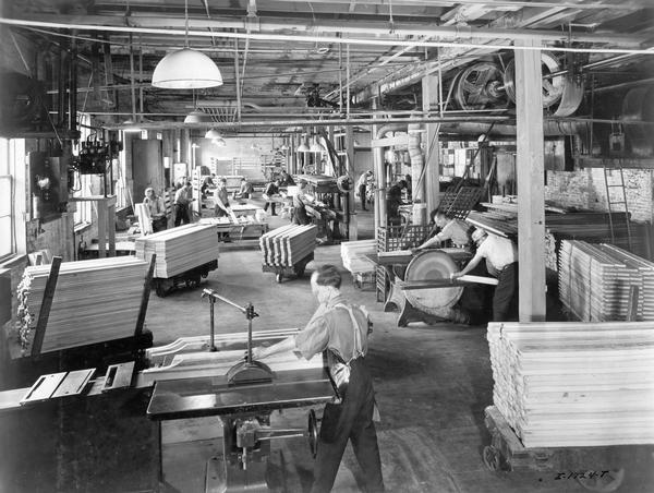 Workers manufacturing, finishing and assembling wooden wagon components at International Harvester's Chatham Works in Ontario, Canada. The factory was owned and operated by the Chatham Manufacturing Company until it was purchased by International Harvester in 1910. The factory produced wagons, sleighs and eventually trucks (1921).