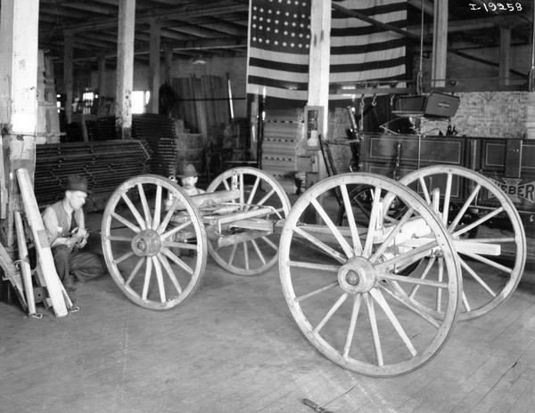 Men working on a wagon truck inside International Harvester's Weber Wagon Works. A completed Weber wagon and a large American flag are in the background. The factory was located at Auburn Park and was owned by the Weber Wagon Company until 1904. International Harvester produced wagons at the factory until 1927.