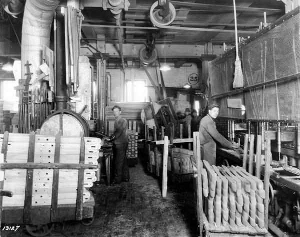 Workers manufacturing wooden wagon components inside International Harvester's Weber Wagon Works. One worker is drilling holes in wooden pieces. The factory was located at Auburn Park and was owned by the Weber Wagon Company until 1904. International Harvester produced wagons at the factory until 1927.