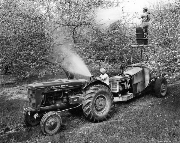McCormick-Deering Model OS-6 orchard tractor in operation in an apple orchard with a 500 gallon Hardie Spray Rig. The rig had a 30-35 gallon pump capacity and was equipped with an International Model U-2 power unit. The equipment was owned and operated by John Humphreys, pictured here on the scaffold atop the spray unit.