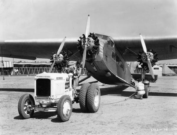 "Crew preparing to pull a damaged Ford Tri-Motor airplane with a white McCormick-Deering I-30 industrial tractor with dual rear wheels at the American Air Races. The races took place at Chicago's Municipal Airport, July 1-5, 1933. A man hitching a tow line to the plane is wearing a jumpsuit with the words ""Aeronautical University"" on the back."