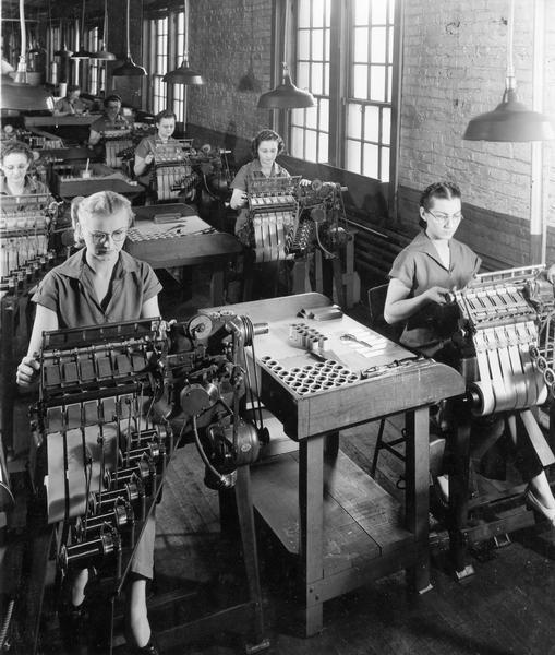 Female workers operating machines at International Harvester's Chatham Works in Ontario, Canada. The factory was originally owned by the Chatham Manufacturing Company. It was purchased by the International Harvester Company in 1910.