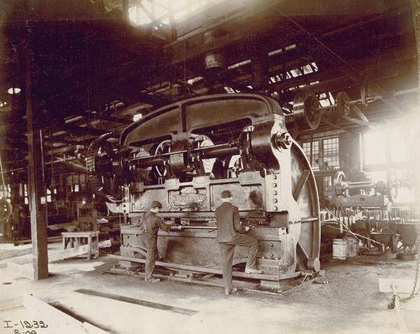 Workers using a large industrial press to manufacture parts in the tool room of International Harvester's Hamilton Works in Ontario, Canada.