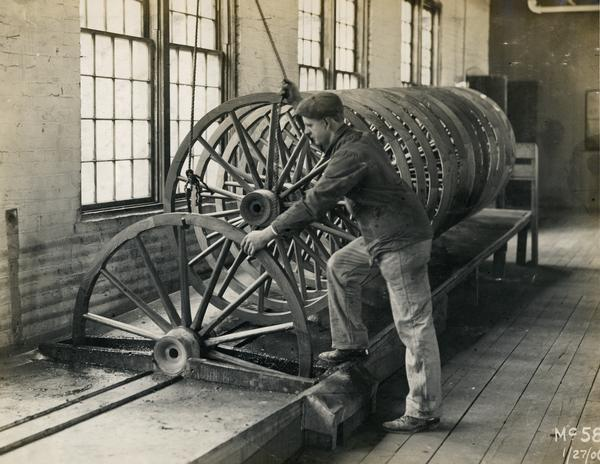 Worker turning a wooden wagon wheel in a groove at International Harvester's Weber Works in Auburn Park.  The factory was owned by the Weber Wagon Company until 1904, when it was purchased by International Harvester.