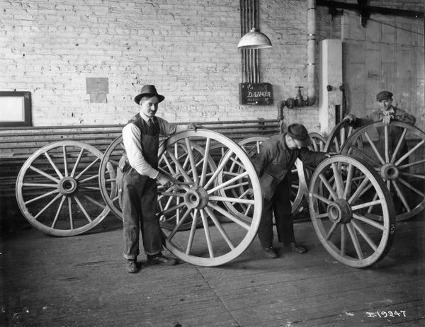 Workers inspecting assembled wagon wheels at International Harvester's Weber Wagon Works in Auburn Park. The factory was owned by the Weber Wagon Company until 1904, when it was purchased by International Harvester.