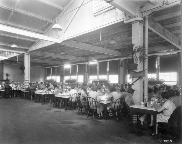 Male and female workers eating lunch inside the cafeteria at International Harvester's Hamilton Twine Mills, Hamilton, Ontario, Canada.