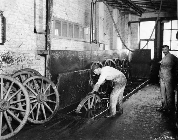 Workers dipping wagon wheels in boiled linseed oil(?) at International Harvester's Weber Wagon Works in Auburn Park. The factory was owned by the Weber Wagon Company until 1904, when it was purchased by International Harvester.
