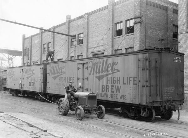Two workmen use a McCormick-Deering I-30 industrial tractor to attach railroad cars carrying Miller High Life beer.