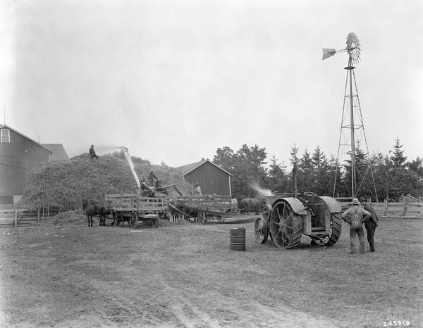 International 15-30 H.P tractor running an International 28 x 46 thresher on a rural farm.  The tractor was purchased by Oscar Krueger in 1920. The thresher was purchased by Mr. Krueger in 1921. He used the tractor and thresher for 11 silo filling and feed grinding jobs totaling 15,000 bushels in 1921.