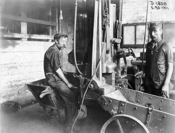 "Two workers in the ""drop hammer malleable foundry"" at International Harvester's Deering Works. The factory was owned by the Deering Harvester Company before 1902. It was located at Fullerton and Clybourn Avenues."