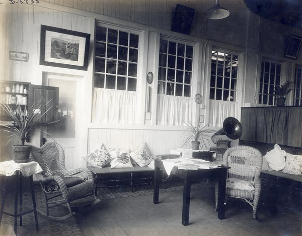 Wicker chairs, pillows, table, magazines, a Victrola, and a medicine cabinet in the infirmary at International Harvester' Deering Works twine mill. The factory was owned by the Deering Harvester Company until 1902, when it became part of International Harvester Company.