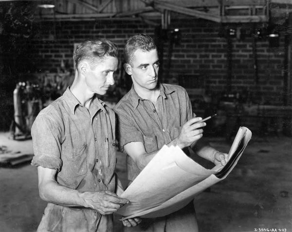 Two men consulting a set of plans as part of a  store modernization project at an International Harvester dealership.