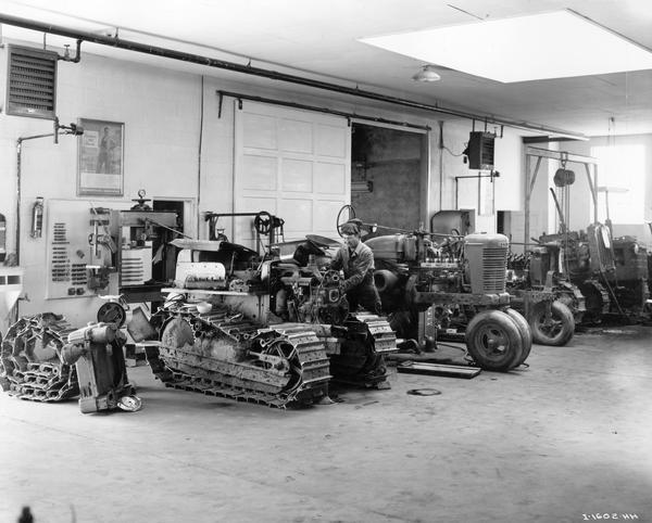 Mechanic taking apart a tractor engine in the service department of the Snake River Equipment Company, an International Harvester dealership. An International diesel TD-6 TracTracTor (crawler tractor), a Farmall M and three other unidentified industrial and farm tractors are also in the shop. The store was managed by George Watkins.